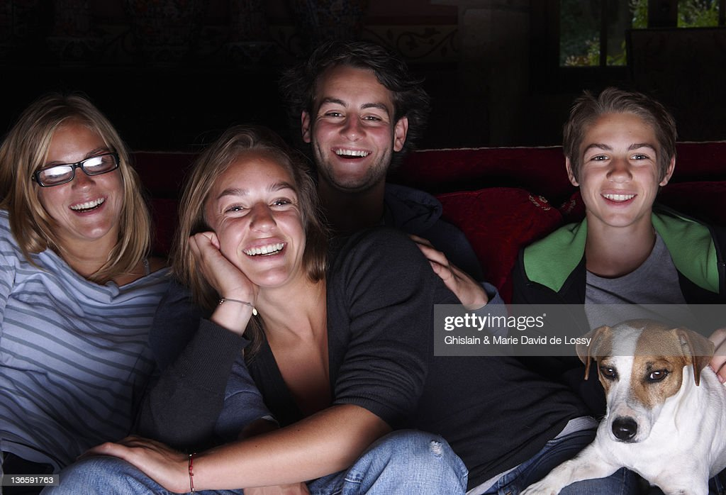 Friends watching television on sofa : Stock Photo