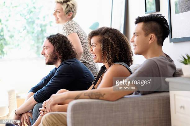 friends watching television on sofa - 20 24 anni foto e immagini stock
