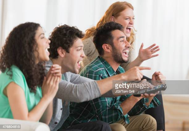 Friends watching television together on sofa