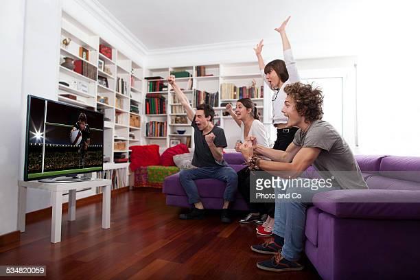 friends watching tv indoors exulting