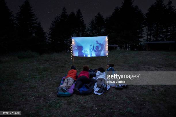 friends watching video on screen at campsite - film stock pictures, royalty-free photos & images