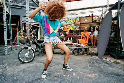 Friends watching woman spinning hoop around thighs - gettyimageskorea