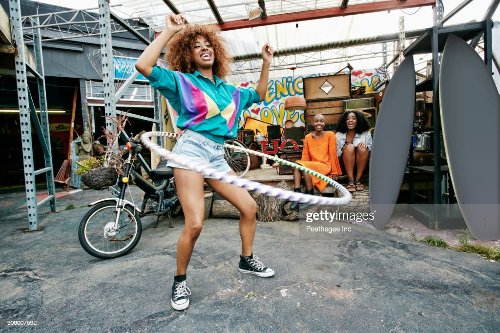 Friends watching woman spinning hoop around waist : Stock-Foto