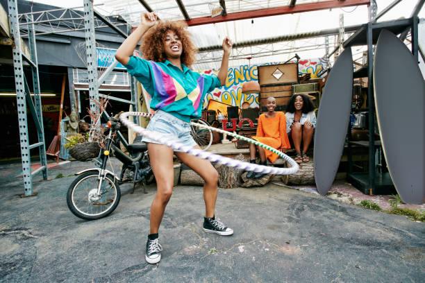 Friends watching woman spinning hoop around waist