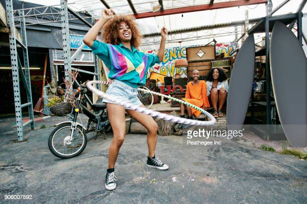 friends watching woman spinning hoop around waist - estilo de vida ativo imagens e fotografias de stock
