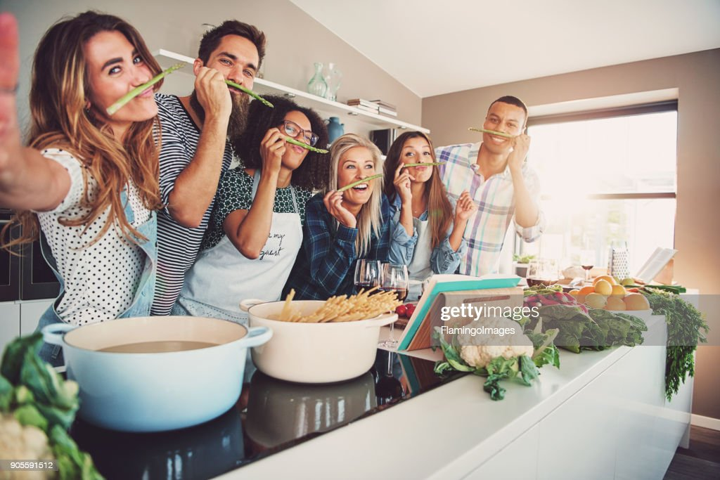 Friends wearing asparagus stalks under their noses : Stock Photo