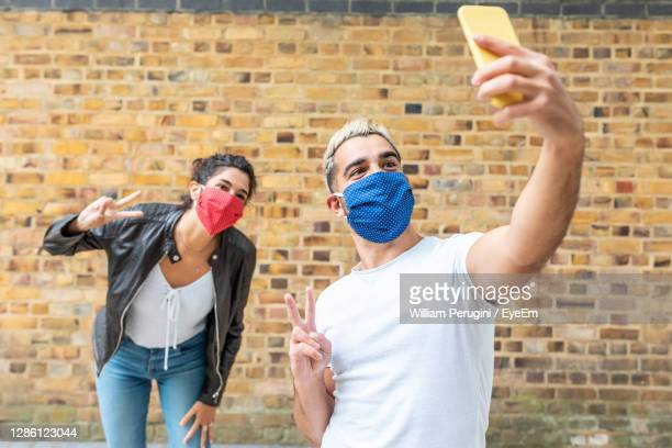friends wearing mask doing selfie against wall outdoors - photographing stock pictures, royalty-free photos & images