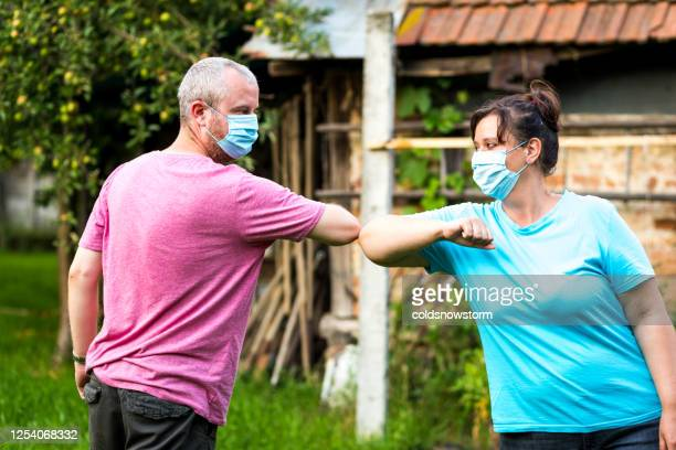 friends wearing masks performing covid-19 elbow bump greeting at home - state of emergency stock pictures, royalty-free photos & images