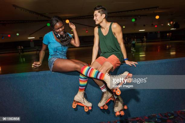 friends wearing roller skates sitting at roller rink - roller rink stock photos and pictures