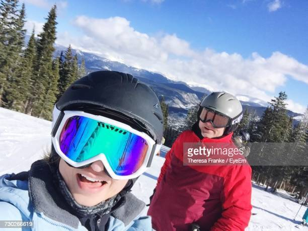 Friends Wearing Ski Goggles And Helmets On Snow Covered Field Against Sky