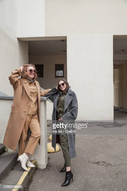 friends wearing sunglasses standing against wall - トレンチコート ストックフォトと画像