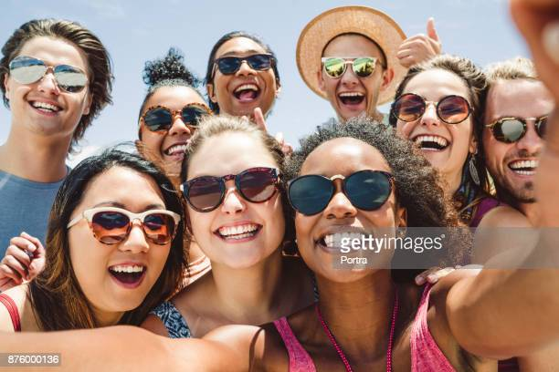 friends wearing sunglasses while taking selfie - sunglasses stock photos and pictures