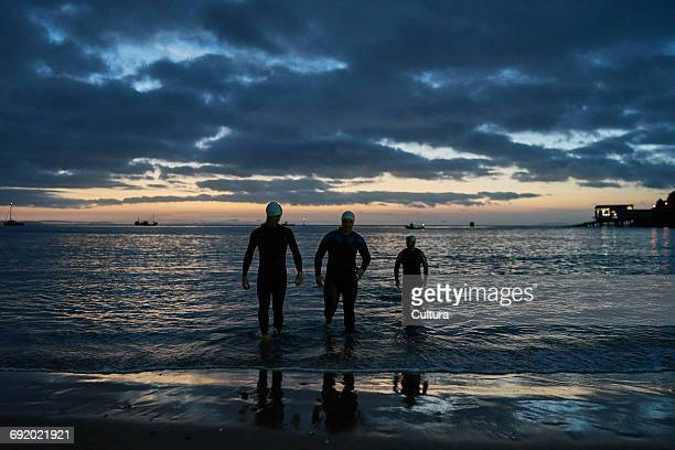 Friends wearing wetsuits ankle deep in water, Tenby, Pembrokeshire, Wales
