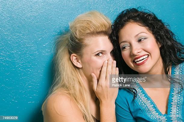 friends whispering - côte à côte photos et images de collection