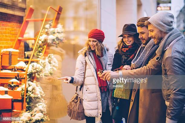 Friends window shopping outdoors in winter city street.