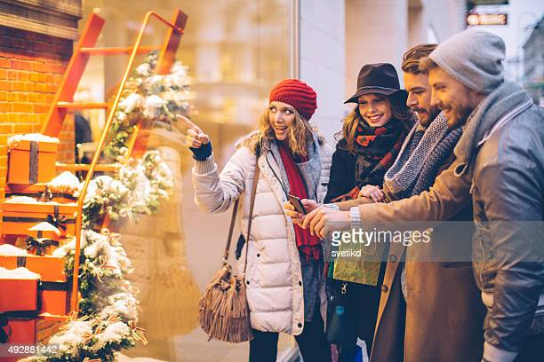 Friends window shopping outdoors in winter city street.