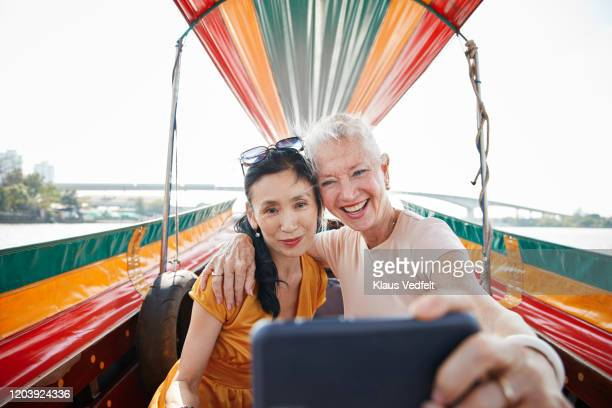 friends with arm around taking selfie in boat - passagier wasserfahrzeug stock-fotos und bilder