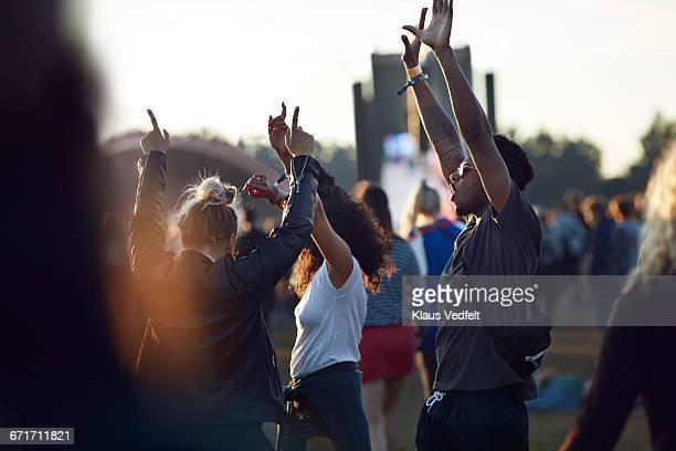 friends with arms in the air at festival concert - mensch im hintergrund stock-fotos und bilder
