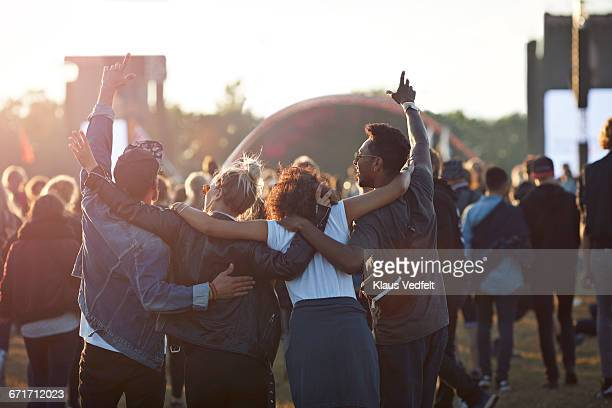 friends with arms in the air at festival concert - music festival stock pictures, royalty-free photos & images