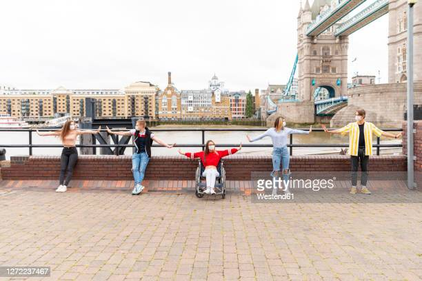 friends with arms outstretched maintaining safe distance in city, london, uk - leaning disability stock pictures, royalty-free photos & images