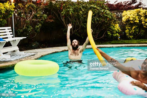 Friends with arms raised playing in backyard pool on summer evening