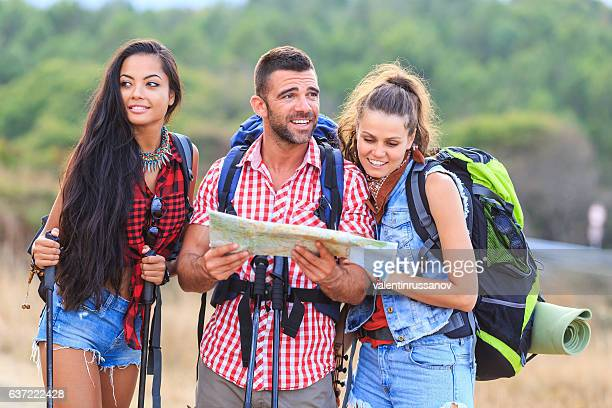 Friends with backpacks and a map hiking in mountain