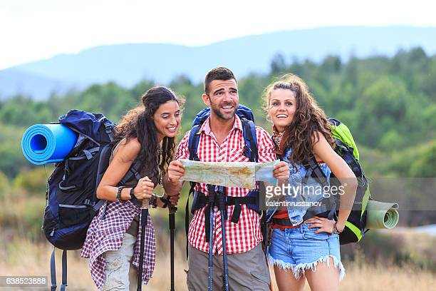 Friends with backpacks hiking and using a map