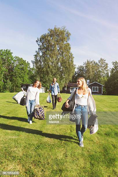 Friends with bags and picnic basket walking on field