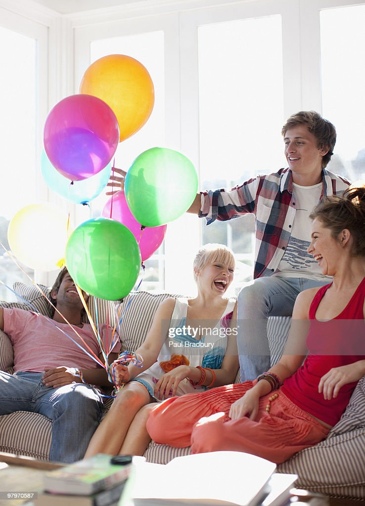 Friends with balloons sitting on sofa in living room : Stock Photo