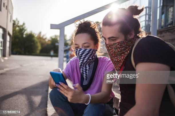 屋外で電話を使用してバンダナと友人 - ゲートル ストックフォトと画像