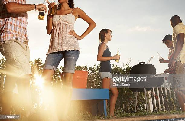 Friends with barbecue and beer bottles enjoying their vacation