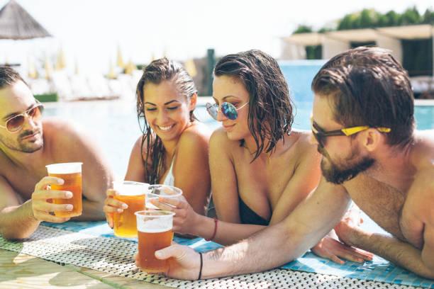 Amis avec de la bière à la piscine