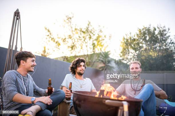 friends with beer bottles by fire pit in yard - fire pit stock pictures, royalty-free photos & images