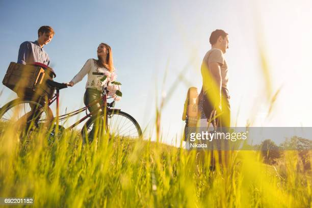 friends with bicycle and picnic box walking on pathway