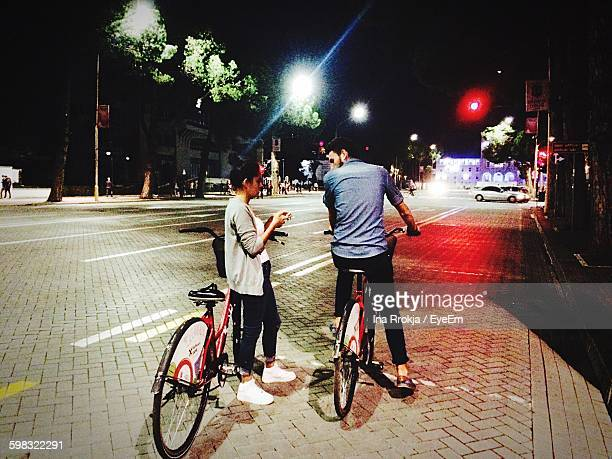 Friends With Bicycle On Footpath In City At Night