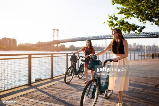 Friends with bicycle walking on promenade against Williamsburg Bridge during sunset