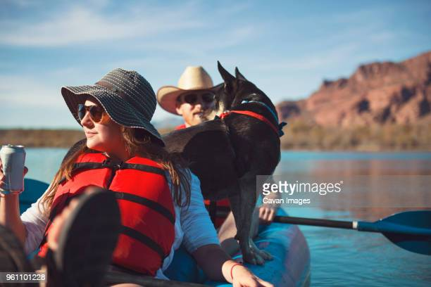 Friends with dog sitting in inflatable kayak on lake