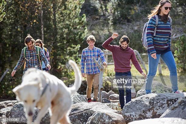 Friends with dog walking on rocks