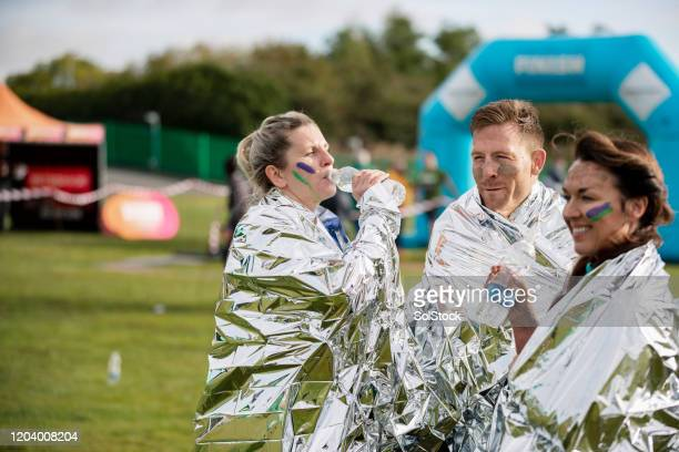 friends with foil blankets drinking water after charity race - competition group stock pictures, royalty-free photos & images