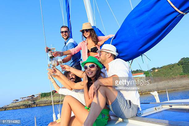 Friends with glasses of champagne on yacht