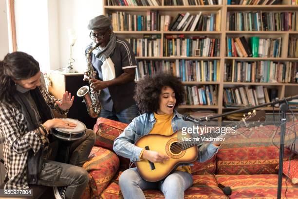 Friends with guiatr and saxophone having fun at home