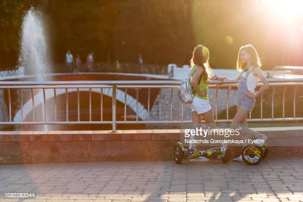 friends with hoverboards standing by railing against bridge - hoverboard stock pictures, royalty-free photos & images