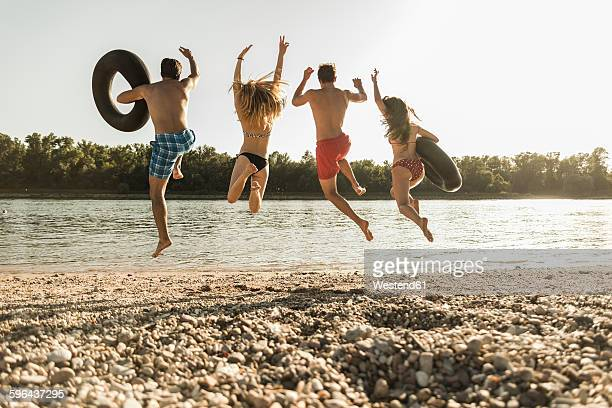 Friends with inner tubes jumping into river