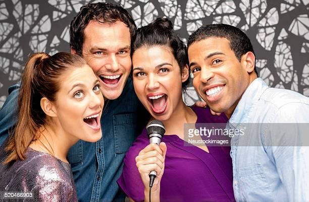 Freunden zusammen mit Mikrofon singen Karaoke im Nightclub