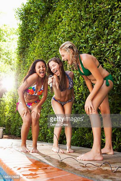 Friends with microphone singing near swimming pool