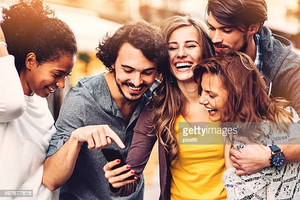 friends with phone outdoors - friends stock pictures, royalty-free photos & images
