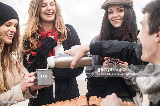 Friends with picnic basket, pouring cups of tea at coast