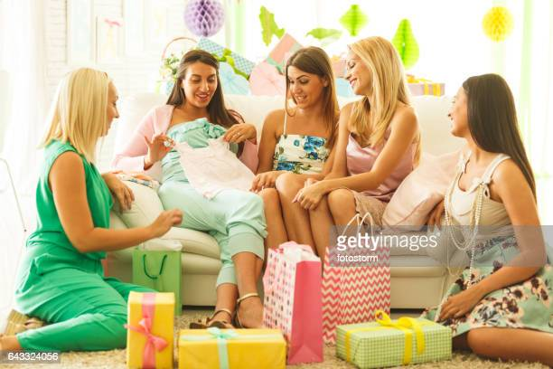 Friends with pregnant woman looking at baby's clothing