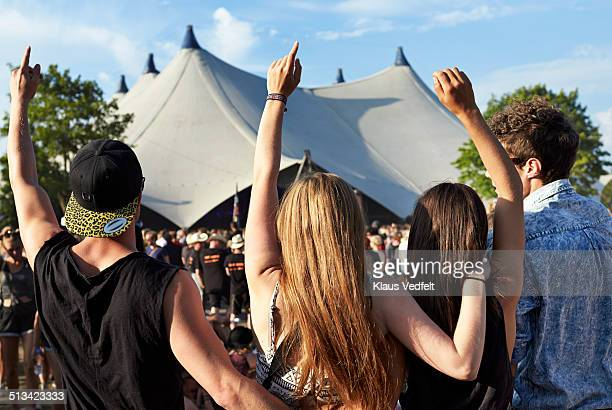 Friends with raised hands at big concert