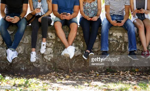 friends with smart phone outdoor - addict stock photos and pictures